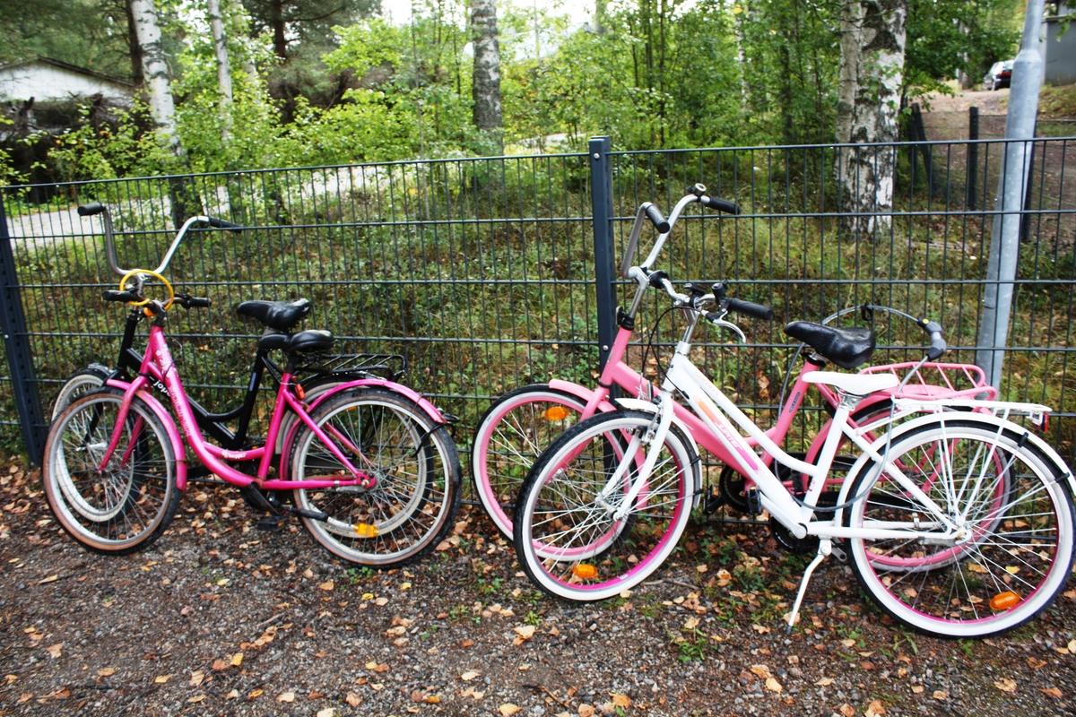 Polkupyöriä nojaamassa koulun piha-aitaan.
