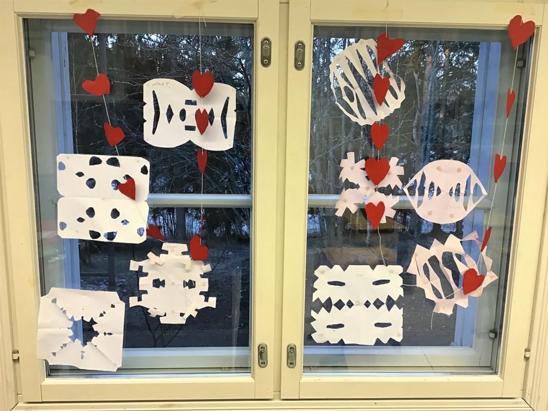Kuvassa on Pullin koulun oppilaiden ikkunataidetta: valkoisesta paperista leikattuja lumikoristeita,  jotka on sinitarralla kiinnitetty ikkunaan.  Niiden vieressä on punaisesta paperista leikattuja pieniä sydämiä, jotka on yhdistetty toisiinsa langalla ja ripustettu ikkunalle roikkumaan.