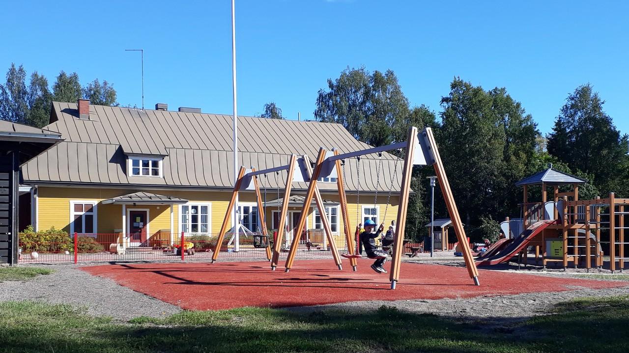 Kuvassa näkyy Kahmon päiväkodin keltainen päärakennus. Etualalla on lapsi keinumassa. Kuvassa näkyy myös kiipeilyteline.